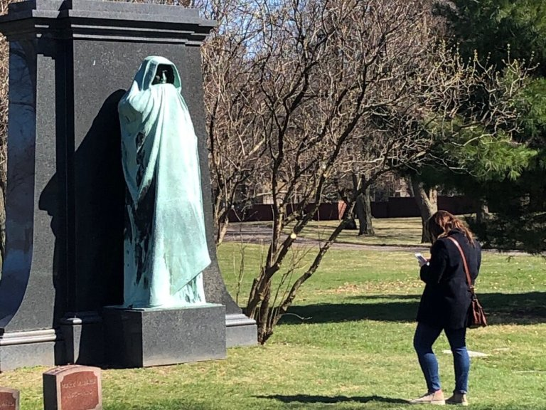 "A masked visitor to Graceland Cemetery in Chicago pays homage to Lorado Taft's sculpture ""Eternal Silence"" early on in the pandemic. (One Illinois/Ted Cox)"